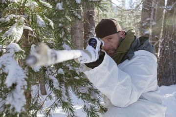 Portrait of a hunter aiming his rifel while hunter in winter conditions.