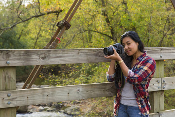 Indian woman shooting a photo on a bridge outside in the fall