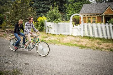A newly married couple bikes through the streets of their neighborhood on their tandem bicycle.