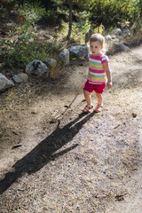 Backlit toddler girl explores on trail with stick near Strawberry, California.