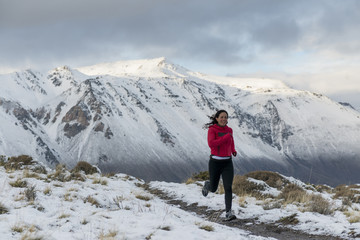 Woman running a snowy dirt trail in Patagonia.