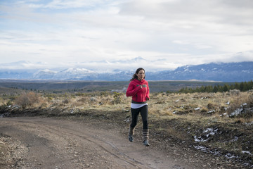 Woman running a dirt road with snowy mountains in the background.