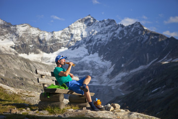 A male hiker enjoys a beer in the last sunlight, during the Glocknerrunde, a 7 stage trekking from Kaprun to Kals around the Grossglockner, the highest mountain of Austria. The Grossglockner mountain is in the background. The beer is called: Hefeweizen, a local brew.