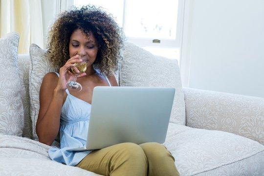 Woman having wine while using laptop