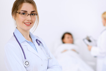 Female doctor smiling on the background with patient and his doctor