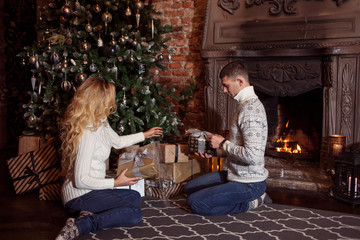 Merry Christmas. Young couple celebrating New Year at home. Man and woman in knitted sweater sitting on the floor by fireplace