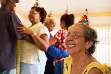 Senior Friends Dancing At Birthday Party In Hospice