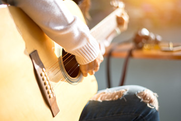 woman's hands playing acoustic guitar, close up, soft and select focus