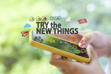 hand holding a smartphone with TRY THE NEW THINGS concept , busi