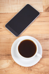 Mobile phone with blank screen and cup of coffee