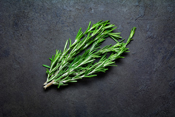 Fresh rosemary springs on black stone background