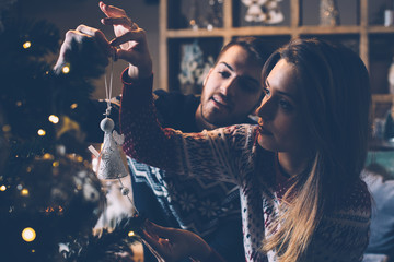 Couple hanging bauble on fir tree