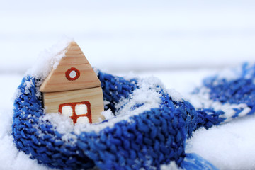 when behind a window snow and cold/ warming blue scarf around a wooden house in the winter season
