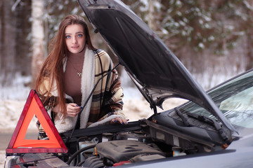 girl wrapped in a blanket placed near the broken car