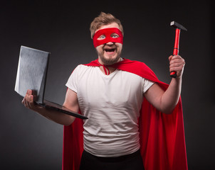 Hacker. Computer repair. Picture of happy smiling super hero man holding laptop computer and hammer isolated on black background in studio.