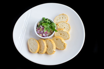 tuna salad with onions, vegetables and toasted bread in white plate and black background