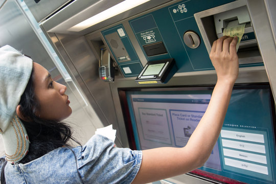 Young woman buys a ticket vending machine
