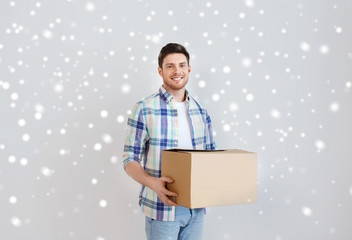 smiling young man with cardboard box at home