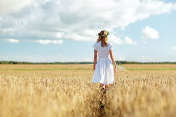 happy young woman in flower wreath on cereal field