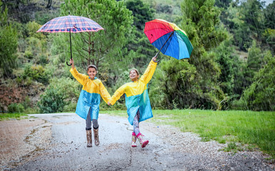 Children with colorful rainbow umbrella and raincoats