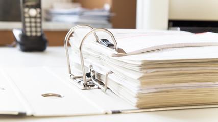 Aktenordner mit Steuerunterlagen für Finanzamt auf Schreibtisch mit Telefon und Drucker im Hintergrund
