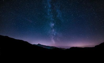 purple night sky stars. Milky way galaxy across mountains. Starr