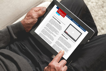 Senior holding a tablet in hands an reading news
