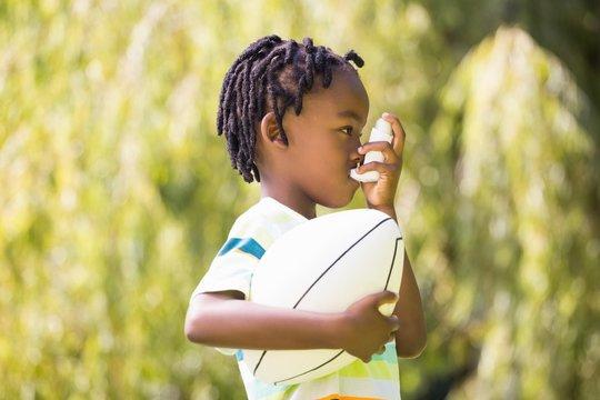 Child is using an asthma inhaler