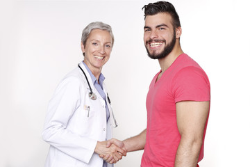Female Doctor Shaking Hands With Male Patient and Smiling