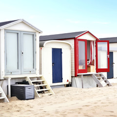 Beach huts or houses at a white beach with blue sky.