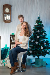 Young married couple in Christmas decorated interior with Eve an