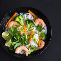 asian rice noodle, shrimps and vegetable soup in bowl