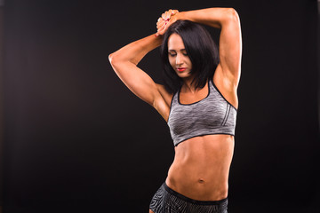 Fitness and sports body concept. Picture of brunette woman with red lips training while posing for photographer isolated on black background in studio.