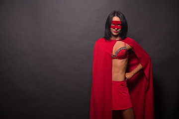 Image of young super hero woman with red mask on isolated on grey background in studio. Brunette lady looking at camera.