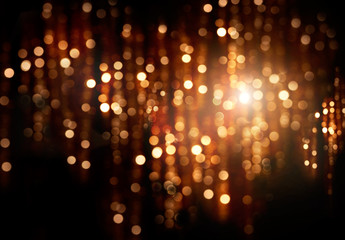 Christmas holiday glowing backdrop. Defocused golden background with blinking stars