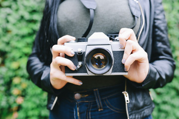 Woman's hands holding analogue camera, close-up