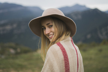 Portrait of smiling young woman wearing hat outdoors