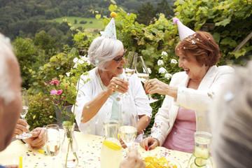 Group of seniors celebrating, drinking champagne