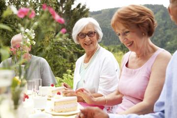 Senior ladies eating cake in garden