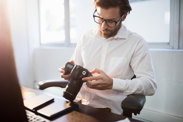 Businessman looking photos on his camera
