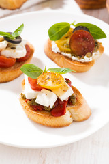 bruschettas with tomatoes and mozzarella on plate, vertical