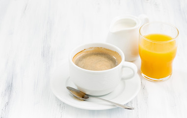 cup of coffee and  orange juice on white table