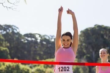 Cheerful winner athlete crossing finish line