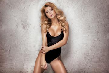 Sensual blonde woman posing in studio.