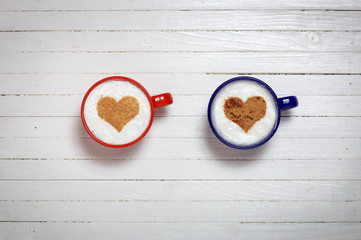 Two cups of coffee with heart shape symbol