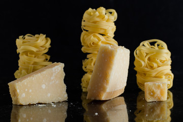 Pasta Tagliatelle, parmesan arranged on marble table.  Delicious dry uncooked ingredients for traditional Italian cuisine dish. Raw closeup background. Top view. Copy space