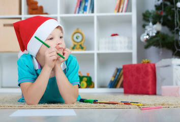 Little boy in Santa red hat going to paint. Christmas concept.