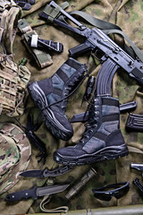 Modern military boots and weapon.Top view/Military boots,rifle,knife and other military equipment.Selective focus