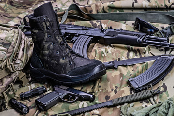 Military boot and weapon.Selective focus/One army boot, pistol, rifle, knife ammo and other ammunition.