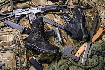Military clothing-shoes and variety of weapons.Top view/Army boots, ax, gun, machete, knife and rifle top view.Selective focus